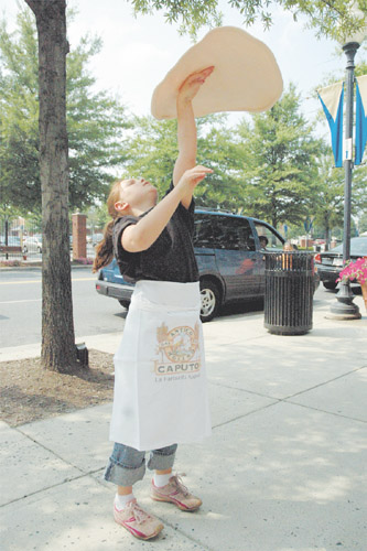 Juliana Zarou, 8, practices throwing dough in front of Don Corleone's Brick Oven Pizzeria is Sterling.